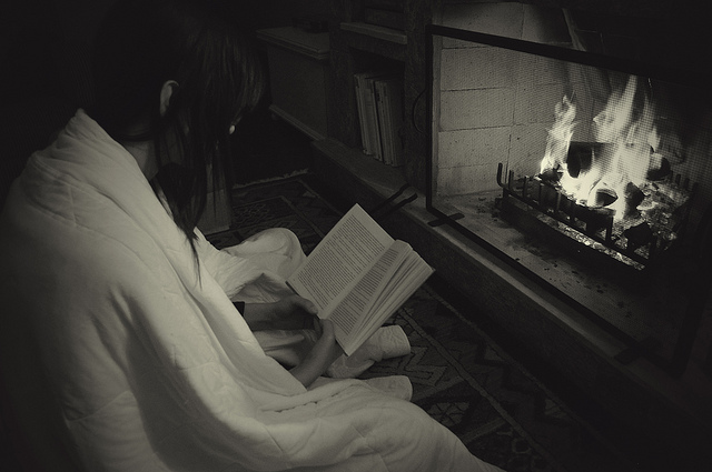 photo of girl reading in front of fireplace