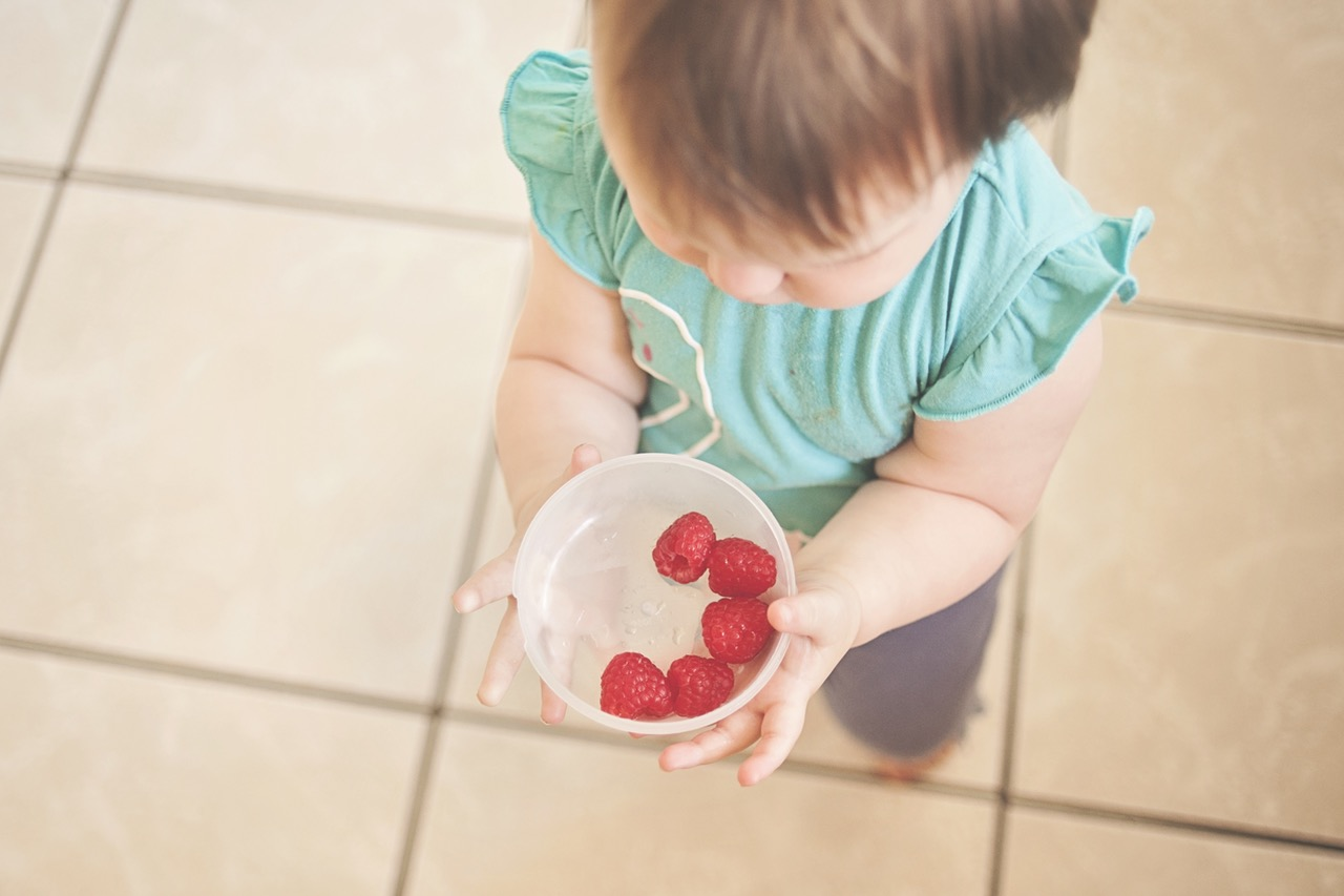 Photo of child holding container of raspberries