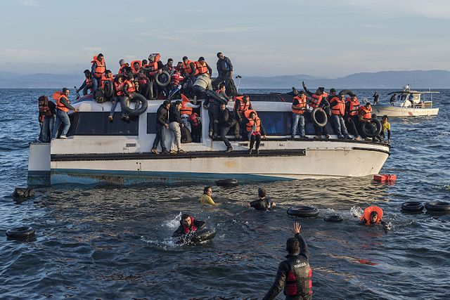 photo of refugees arrive in Greece via life boat