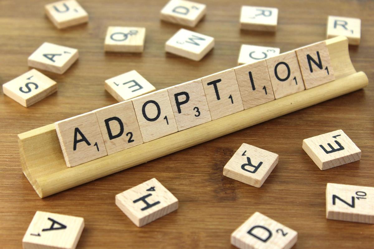Adoption spelled with Scrabble tiles