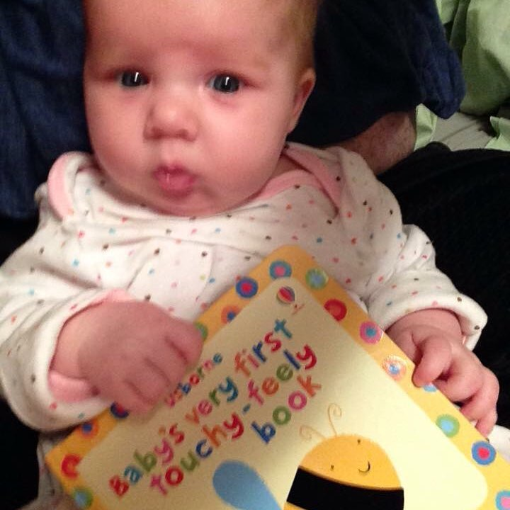 2 month old Rebekah Clay with a book