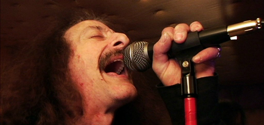photo of musician singing into microphone