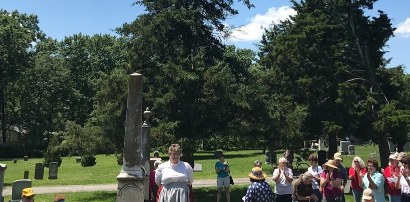 photo of reenactor performing in cemetery with audience