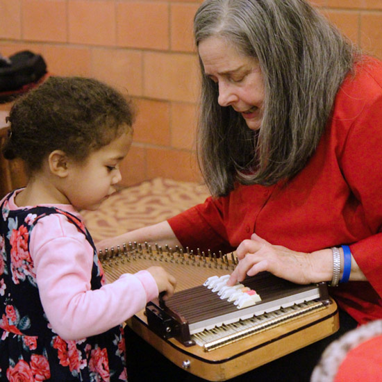 storyteller Beth Horner shows a young child how to play the autoharp at a library program
