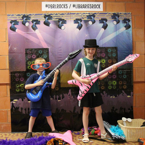 kids playing dress up with inflated guitars and concert backdrop
