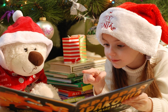 child reading with teddy bear