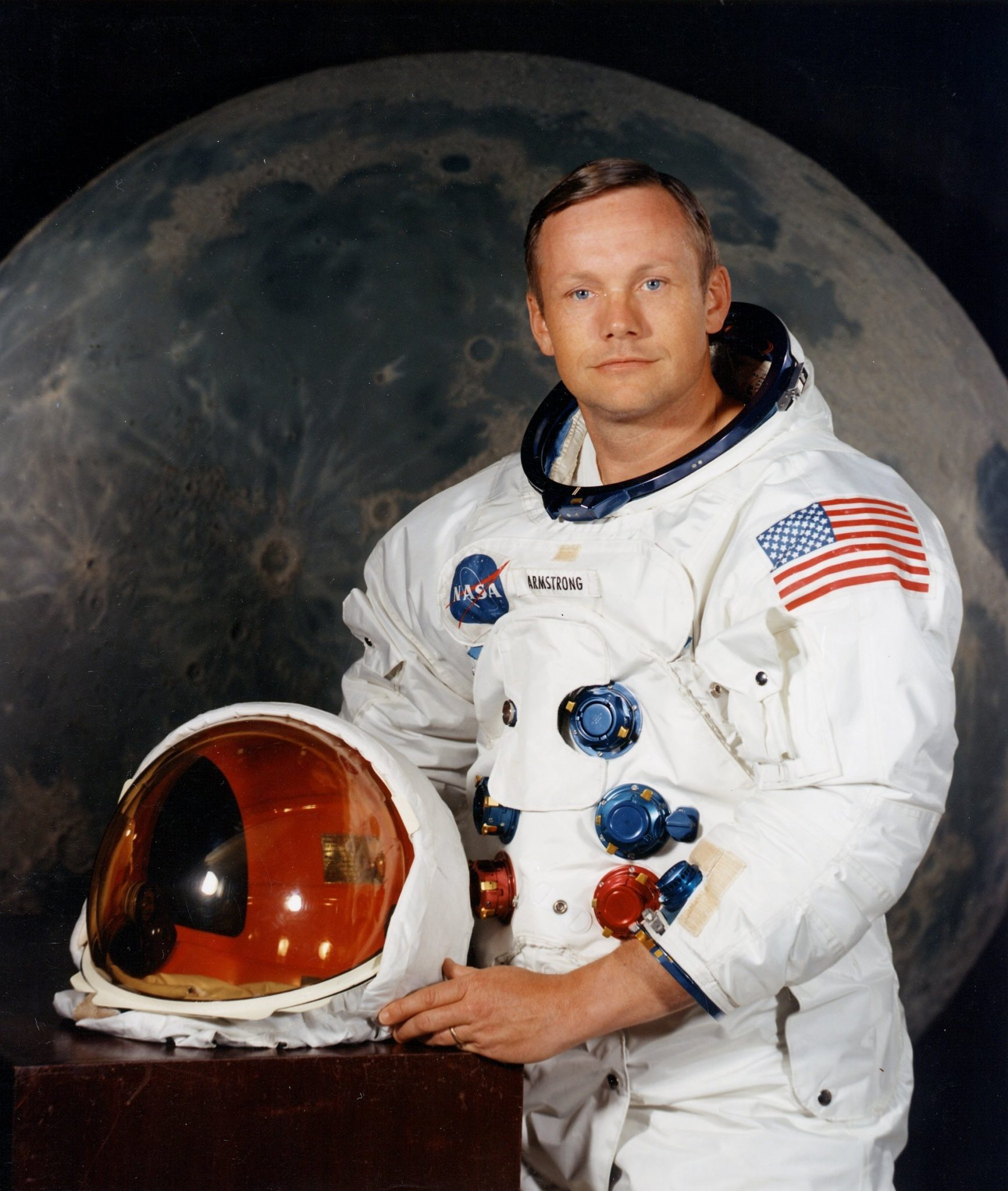 Neil Armstrong posing in front of moon backdrop while in astronaut gear holding helmet