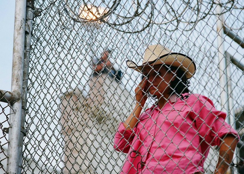 woman in pink western shirt and a cowboy hat standing behind a barbed wire-topped fence