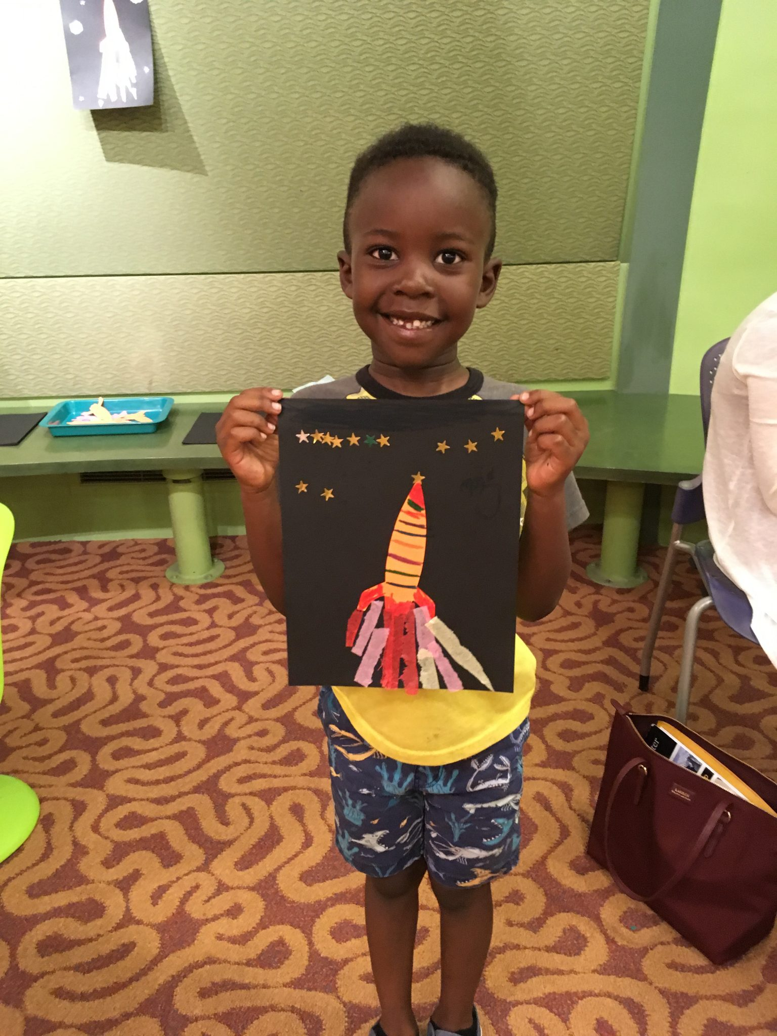 child holds up finished rocket art