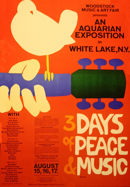 "Woodstock poster, dove sitting on guitar neck, with words ""3 days of peace and music"" on orange background"