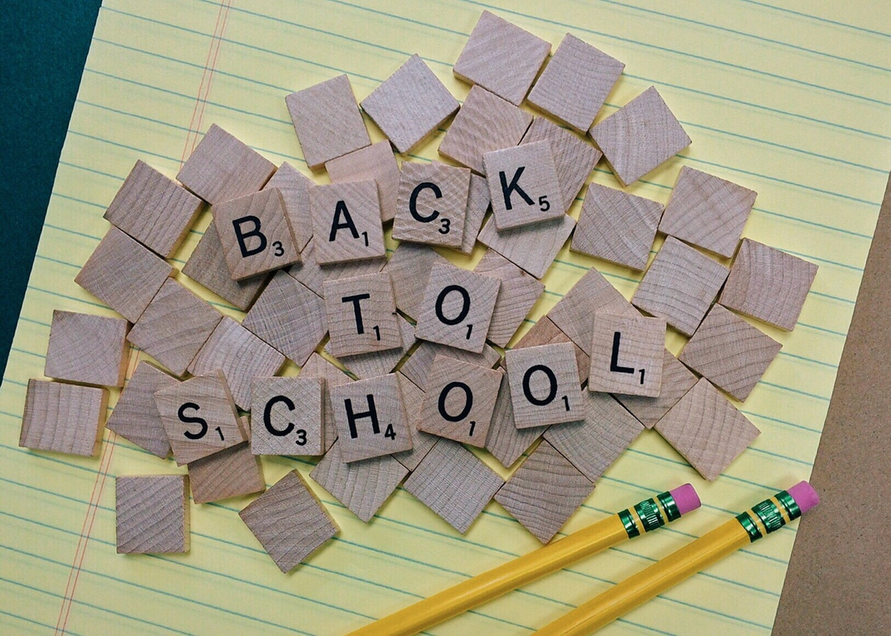 """yellow legal pad with pencils and scrabble tiles on top, tiles spelling """"back to school"""""""