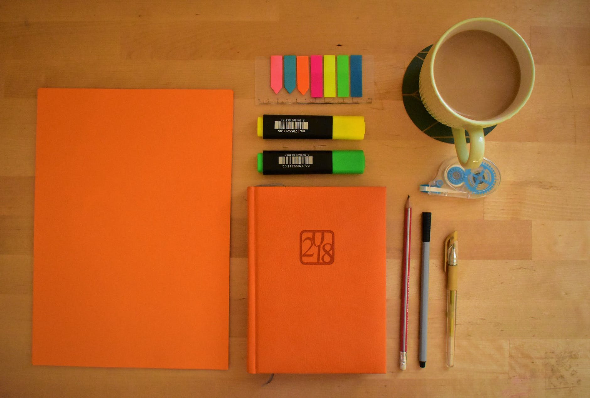 orange jounral on table with pens and coffee