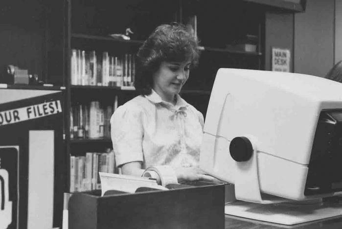 library staff member at '80s-era computer monitor
