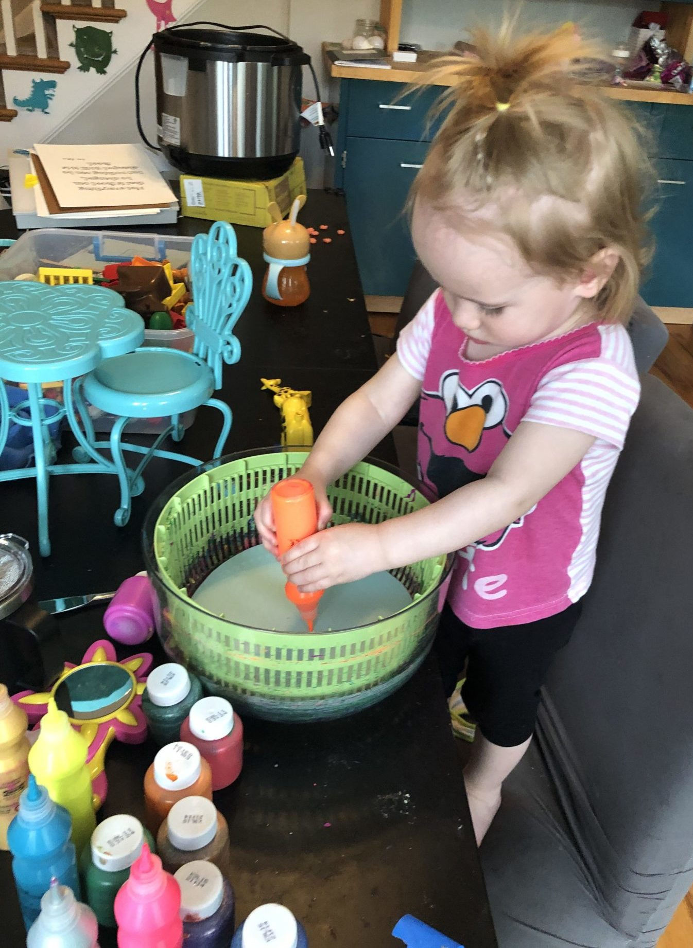 child squeezing paint into salad spinner