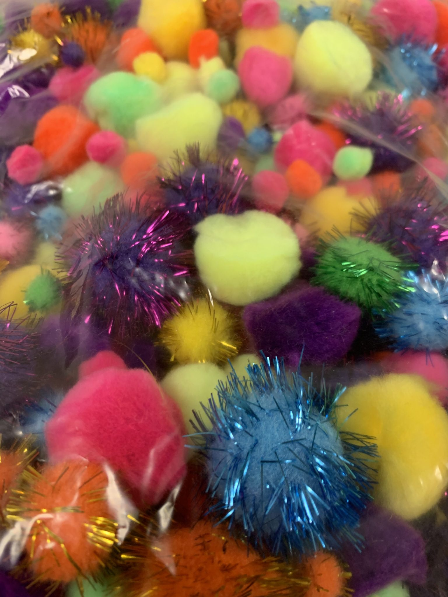 Clear plastic bag of multicolored pom-poms.