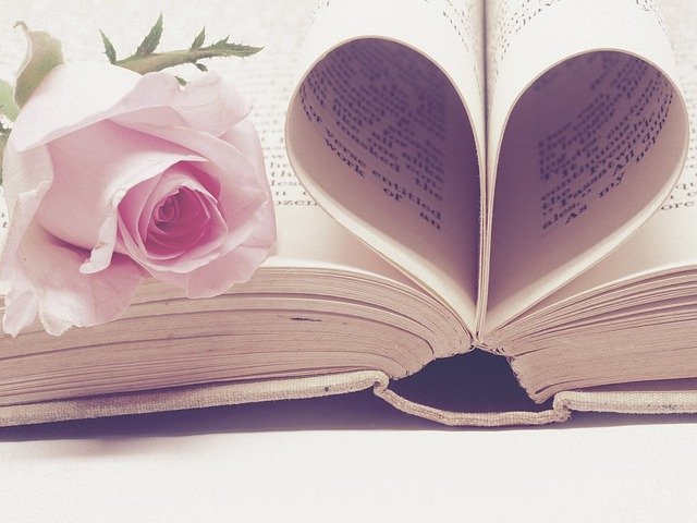 book pages folded into a heart with a pink rose