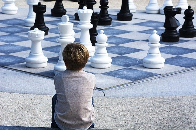 boy sitting looking at giant chess board