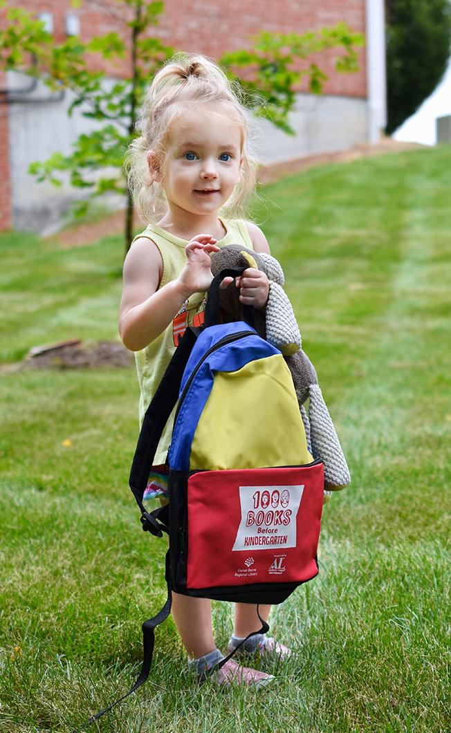 girl holding the Daniel Boone Regional Library's 1,000 Books Before Kindergarten backpack